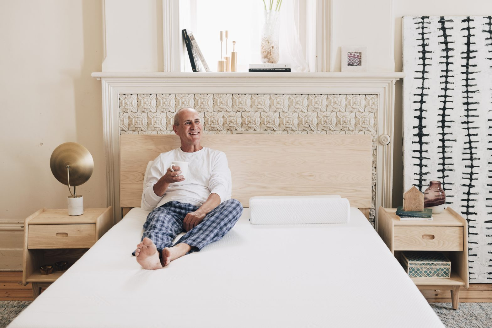 Image of a man in his 50-60's sitting upright in bed with a drink in his hand, looking off camera