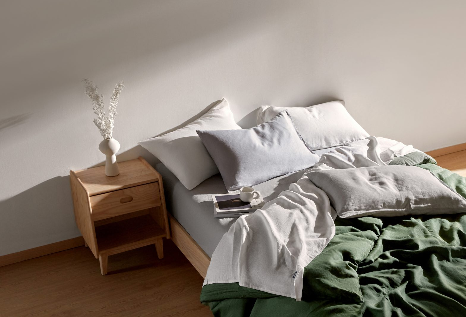 Image of a bed with earthy green Ecosa sheets.