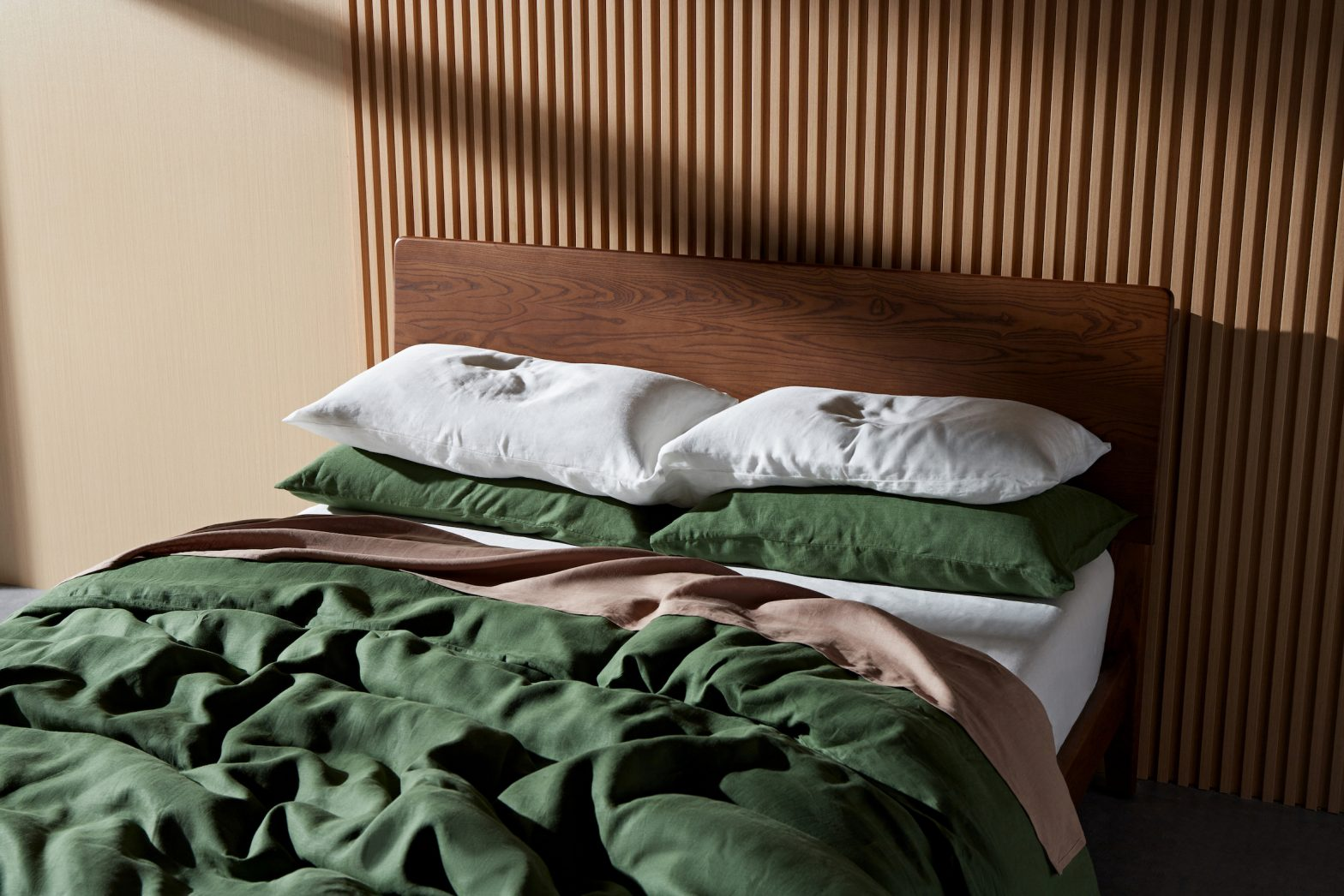 Green flax linen sheets on a bed,