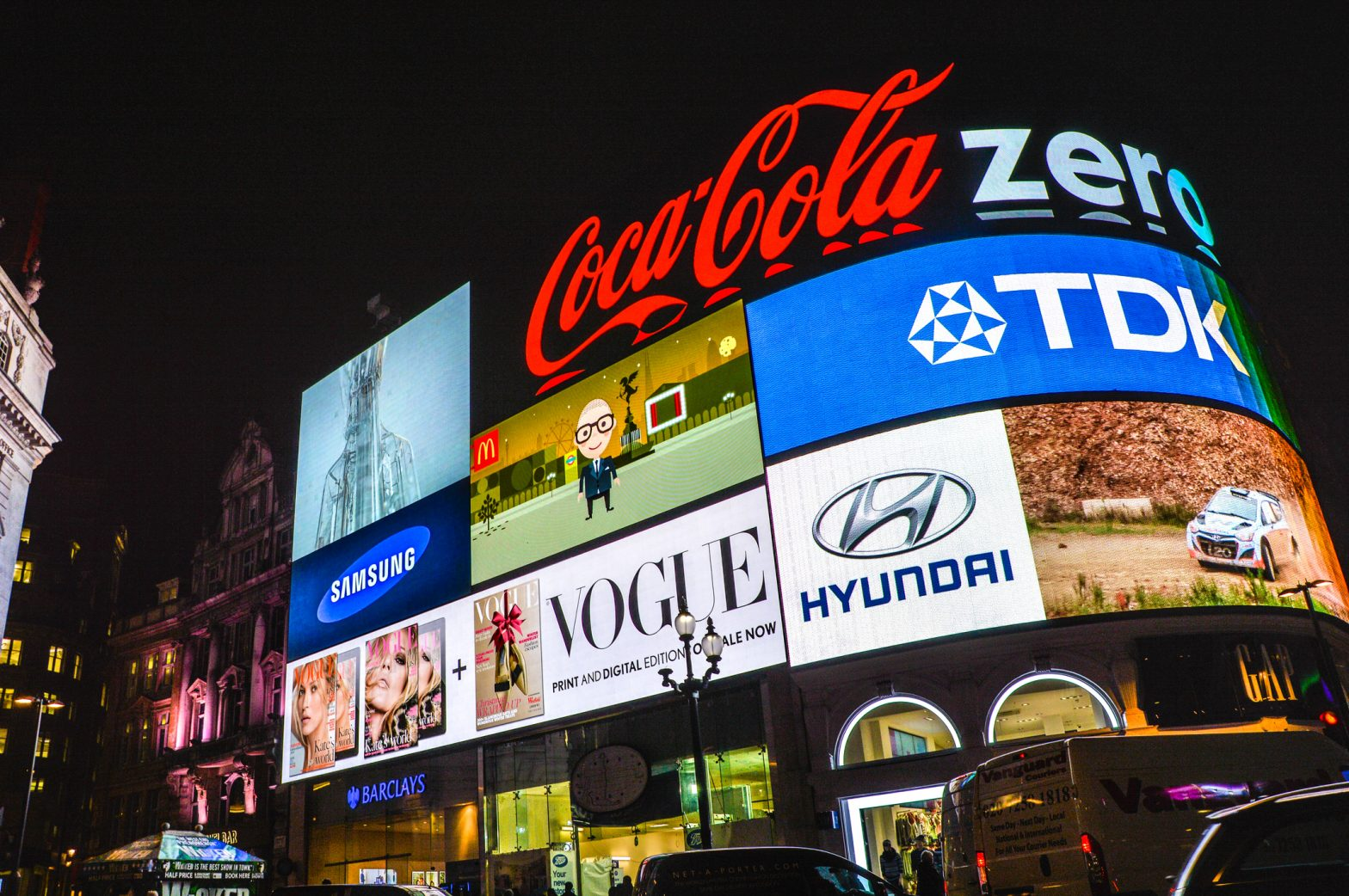 A billboard covered in adverts and brand logos,