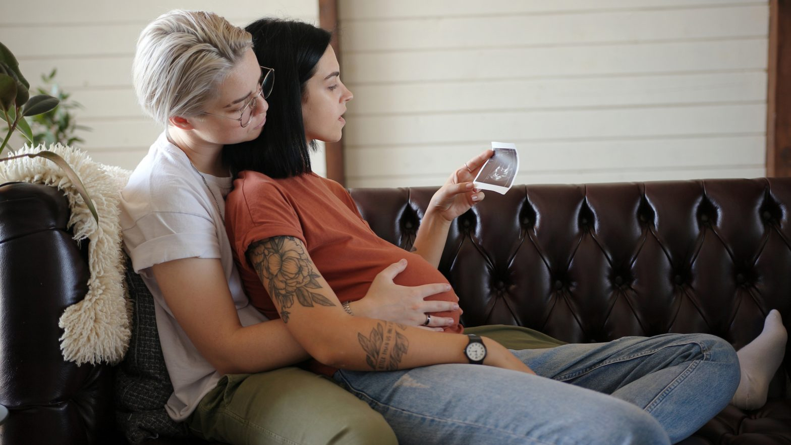 Blonde runs hands on pregnant girlfriend belly and brunette holds
